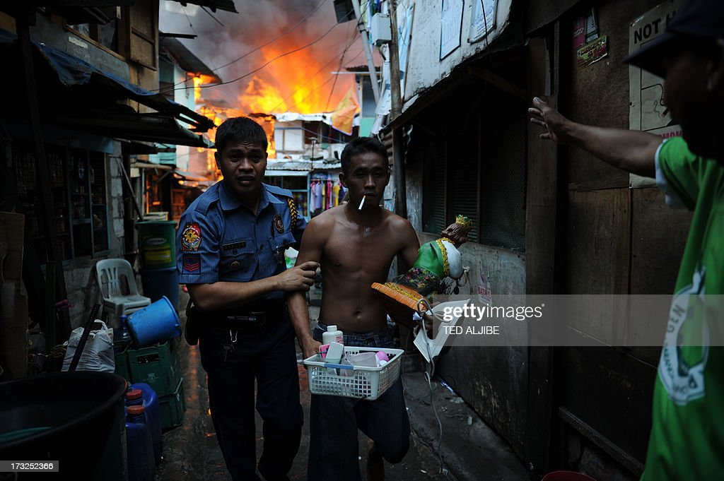 A policeman (L) leads out a resident carrying salvaged belongings from his burning house as a fire engulfs a shanty town in the financial district of Manila on July 11, 2013, leaving more than 1,000 people homeless according to city officials. There were no immediate reports of casualties from the blaze, which occurred mid-morning amid government plans to relocate thousands of families living in areas vulnerable to floods and typhoons.