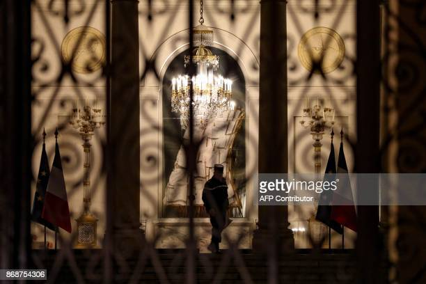 A policeman leaves by the main entrance of the Elysee palace at night in Paris on October 31 2017 / AFP PHOTO / LUDOVIC MARIN