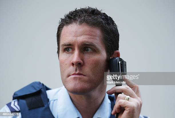 Policeman listens to a radio on Philip St near the Lindt Cafe Martin Place on December 15 2014 in Sydney Australia Police attend a hostage situation...