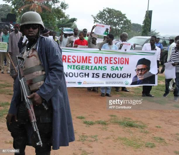 A policeman looks as protesters carry placards in the rain to demand that ailing President Mohammadu Buhari resume work or resign in Abuja on August...