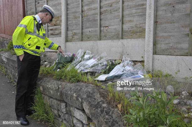 A policeman looks at floral tributes on a wall near the pavement where 11yearold Sam Riddall died after a car ploughed into him and his friends on...