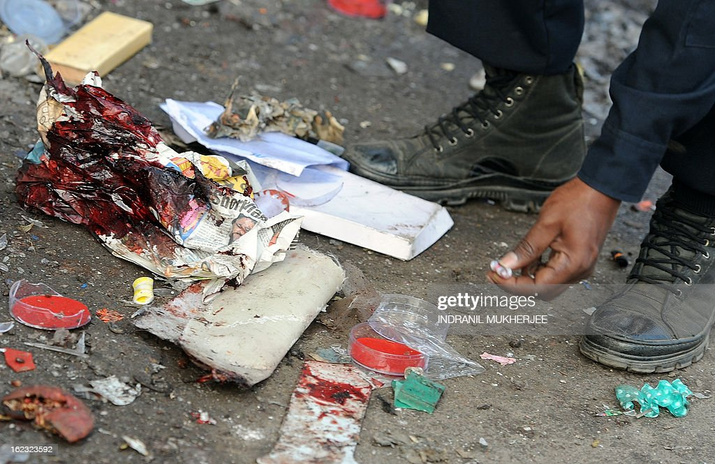 A policeman looks for clues next to a blood stained newspaper at one of the blast sites at Dilsukh Nagar in Hyderabad on February 22, 2013 the morning after twin bomb attacks killed 14 people and wounded dozens more. The bombings, the first to hit India since 2011, hit a mainly Hindu district in Hyderabad, a hub of India's computing industry which hosts local offices of Google and Microsoft among others and which has a large Muslim population. AFP PHOTO / Indranil MUKHERJEE