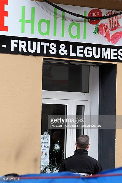 A Policeman looks for evidence at a Muslim butcher's shop that was sprayed with bullets overnight on February 3 2016 in Propriano on the French...