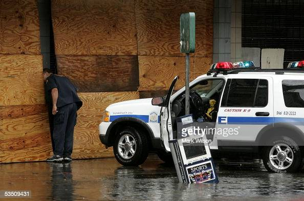 A policeman looks inside a building on Canal Street after Hurricane Katrina hit the area August 29 2005 in New Orleans Louisiana Katrina was down...