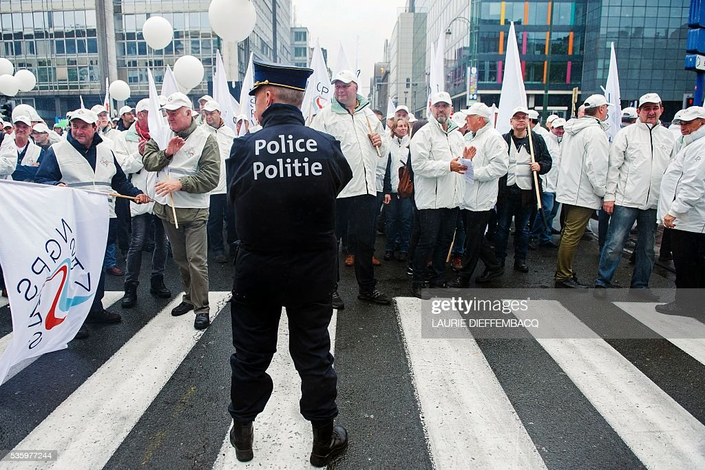 A policeman looks on as workers of the public services main trade unions gather for a demonstration on May 31, 2016 in Brussels. Christian democrat union ACV-CSC and Socialist union ACOD-CGSP of the public services were striking and holding a demonstration today against measures introduced by the Federal Government. / AFP / Belga / LAURIE DIEFFEMBACQ / Belgium OUT