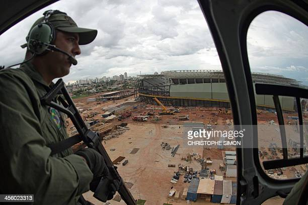 A policeman looks on with the Arena Pantanal stadium under construction on background in Cuiaba Mato Grosso State Brazil on 12 December 2013 The...