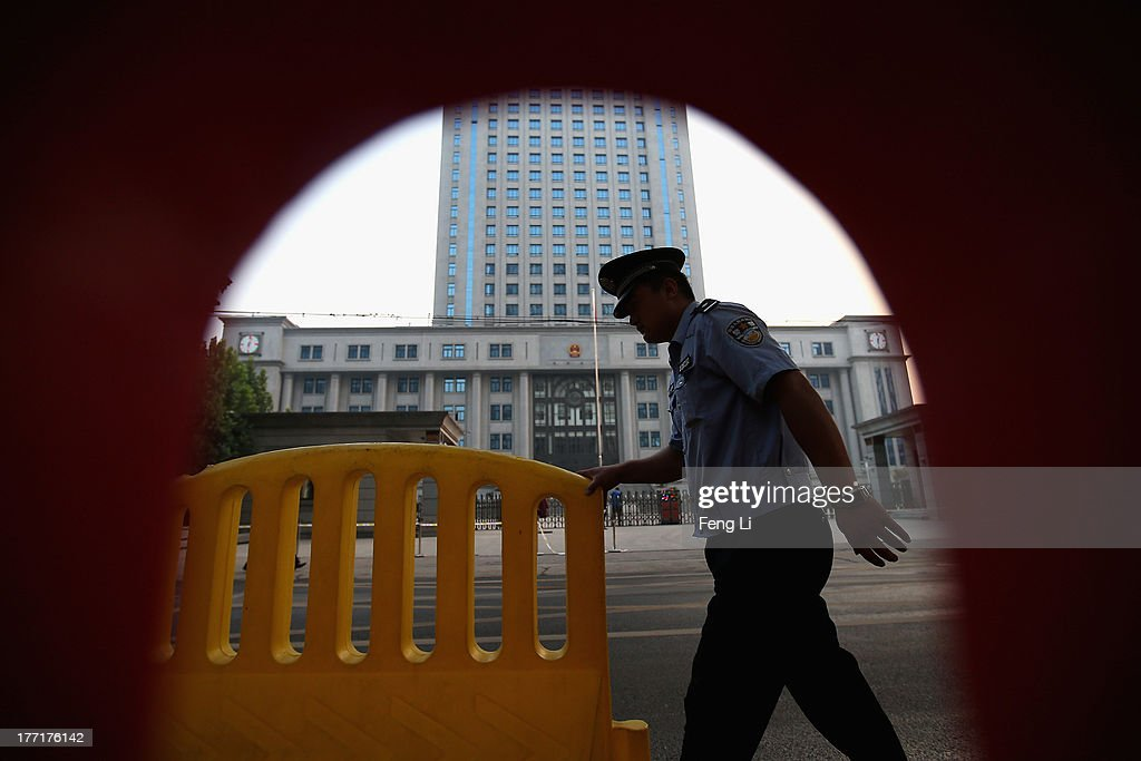 A policeman moves the fence passing the Jinan Intermediate People's Court on August 22, 2013 in Jinan, China. Former Chinese politician Bo Xilai is standing trial on charges of bribery, corruption and abuse of power. Bo Xilai made global headlines last year when his wife Gu Kailai was charged and convicted of murdering British businessman Neil Heywood.