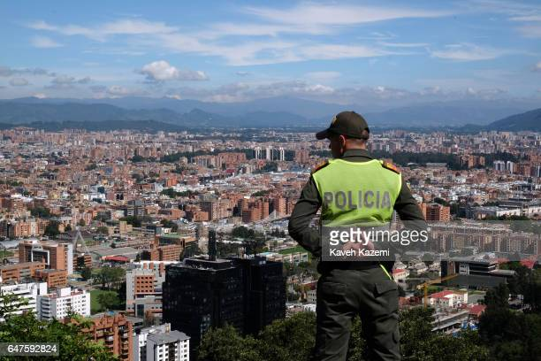 A policeman on duty stands with Bogota's skyline in the background on the spot known as 'Mirador de la Paloma' on La Calera road or better known as...