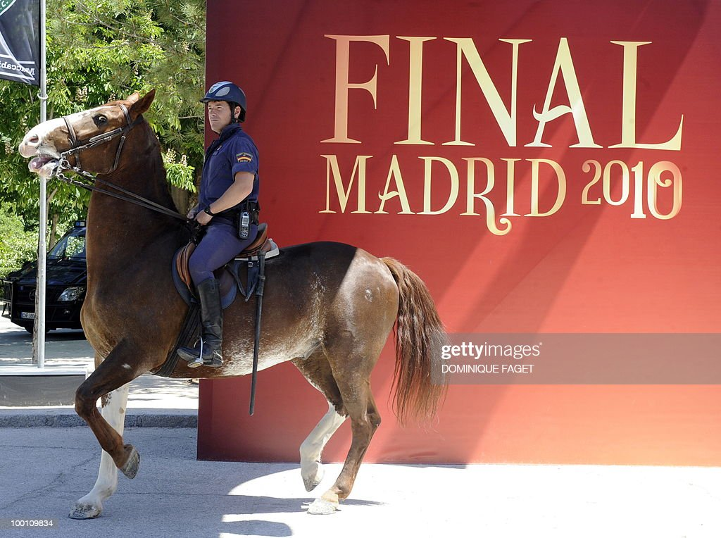A policeman on horseback passes a banner publicising the upcoming UEFA Champions League final match at the Retiro Park in Madrid on May 21, 2010. Inter Milan will face Bayern Munich for the UEFA Champions League final match to be played at the Santiago Bernabeu Stadium in Madrid on May 22, 2010.