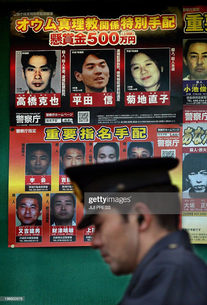 A policeman passes before pictures of suspected former members (top three) of Japan's Aum Supreme Truth doomsday cult including Makoto Hirata (C) who was arrested in Tokyo on January 1, 2012 after almost 17 years on the run. Hirata, 46, turned himself into a police station in Tokyo, just 10 minutes before midnight on New Year's Eve.