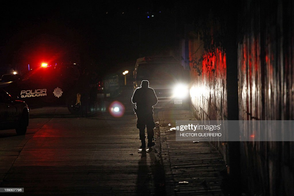 A policeman patrols a crime scene where human remains were found in Guadalajara city on January 11, 2013. Two men and one woman were beheaded and abandoned on a street inside trash bags. AFP PHOTO/Hector Guerrero