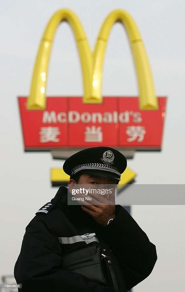 A policeman patrols near the opening ceremony for a new McDonald's drive-thru facility on January 19, 2007 in Beijing, China. McDonald's opened its first restaurant in mainland China in 1990, in Shenzhen, Guangdong province and now operates 760 restaurants countrywide, which employ over 50,000 people.