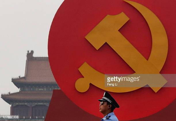 A policeman patrols under a giant communist emblem on the Tiananmen Square on June 28 2011 in Beijing China This year's celebrations will mark the...