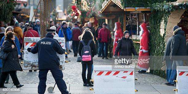 A policeman places concrete elements in front of the 'Striezelmarkt' Christmas market in Dresden eastern Germany on December 20 as security measures...
