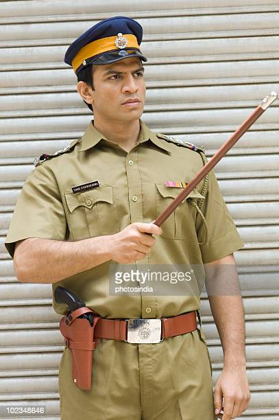 Policeman pointing away with a nightstick