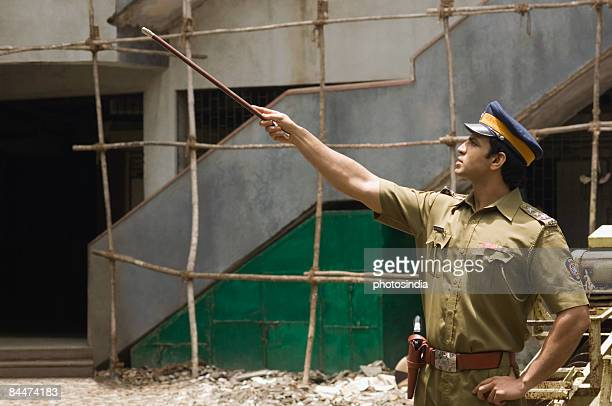 Policeman pointing forward with a nightstick