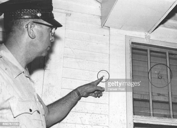 Policeman Points Out Bullet Holes in Witness' House Patrolman Frank Antonio shows holes in wall and window of home of Hal W Eastman 2125 S Williams...