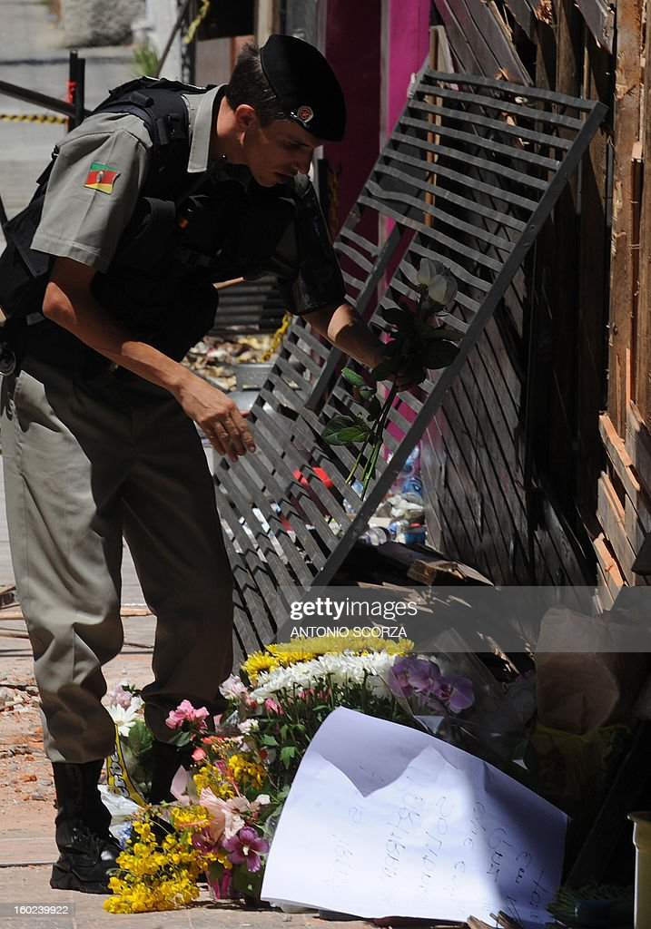 A policeman puts flowers in front of the facade of the Kiss nightclub where a blaze on the eve killed more than 230 people, on January 28, 2013 in Santa Maria, southern Brazil. AFP PHOTO / ANTONIO SCORZA