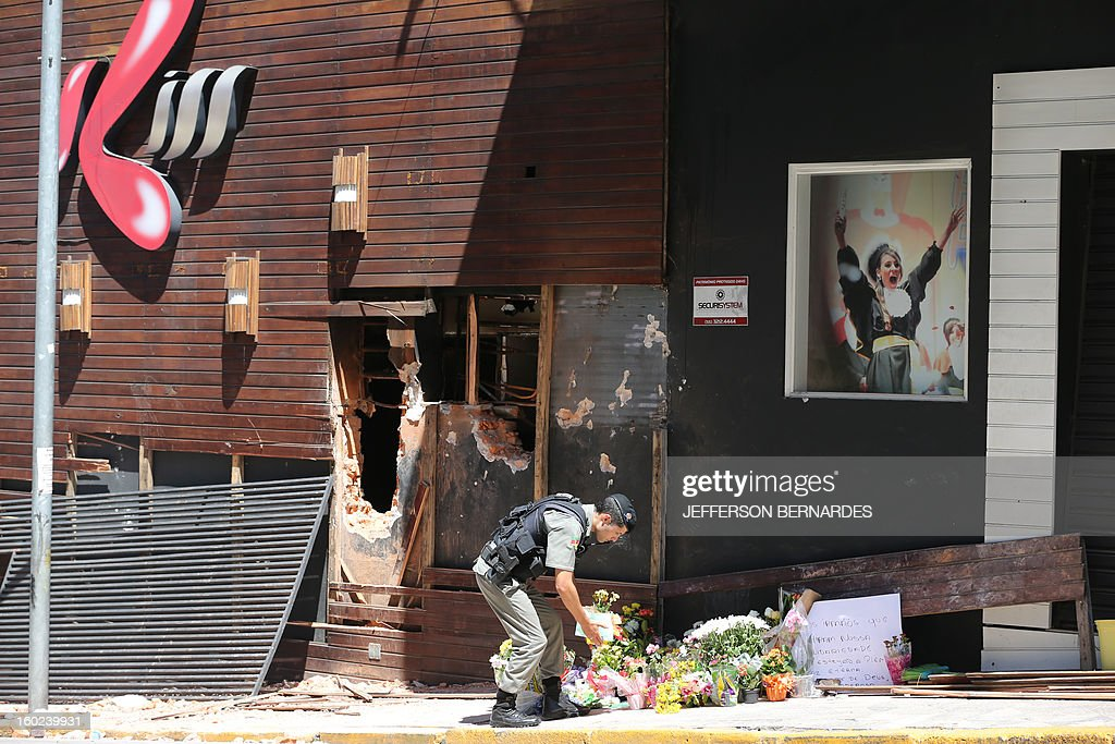 A policeman puts flowers in front of the facade of the Kiss nightclub where a blaze on the eve killed more than 230 people, on January 28, 2013 in Santa Maria, southern Brazil. AFP PHOTO / JEFFERSON BERNARDES