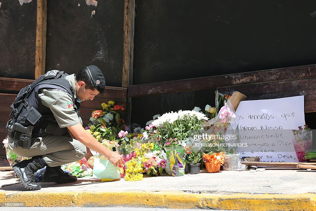 A policeman puts flowers in front of the facade of the Kiss nightclub where a blaze on the eve killed more than 230 people, on January 28, 2013 in Santa Maria, southern Brazil.