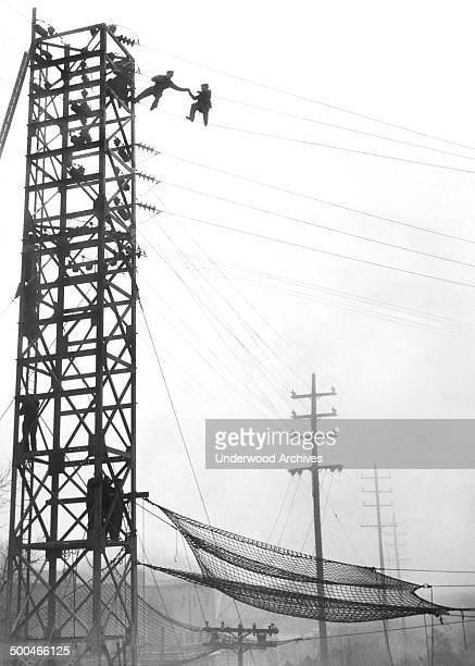A policeman reaches out and grabs a man on high tension power lines before he can carry out his threat to jump New York New York December 4 1939 The...