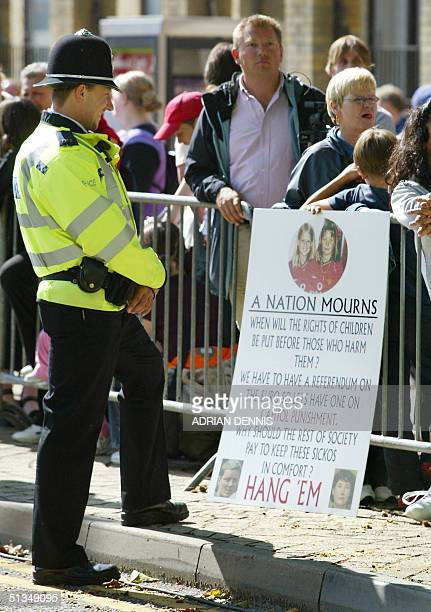 A policeman reads a placard outside Peterborough Magistrates Court 10 September 2002 while Ian Huntley the man accused of murdering schoolgirls Holly...