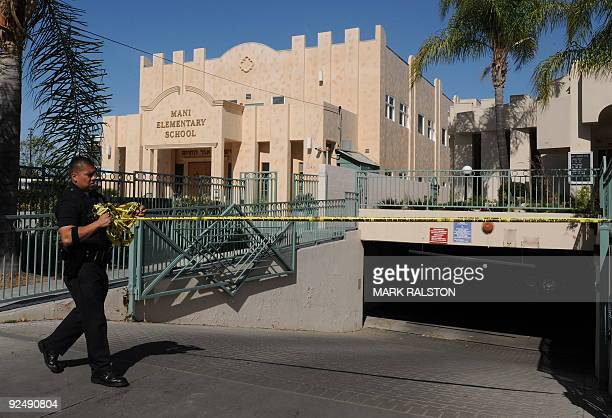 A policeman removes crime scene tape from the entrance to the underground car park at the Adat Yeshurun Sephardic Congregation where two Jewish men...