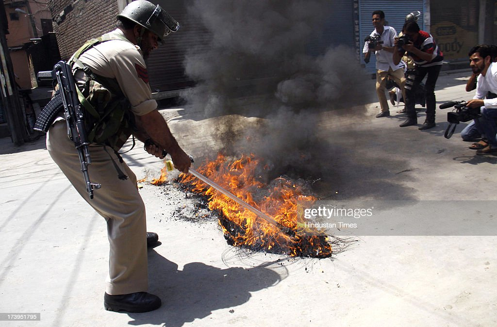 Policeman removing a burning tire during a protest against killing of 4 people in BSF firing on July 18, 2013 in Srinagar, India. Four people were killed today when security personnel opened fire at a mob that had gathered at a BSF camp in Ramban district protesting against alleged manhandling of an Imam of the area by the force. Curfew would be imposed in Srinagar and all other major towns in the Kashmir Valley from Friday morning as a precautionary measure.