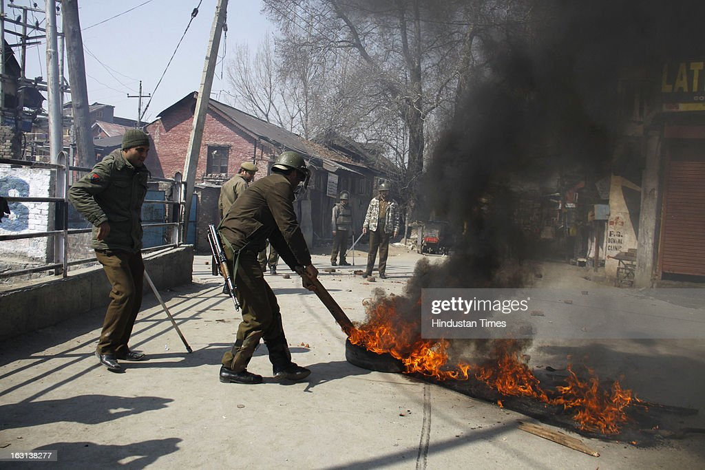 Policeman removing burning tyres during a strike to protest the death of 28 year old Kashmiri student, Mudassir Qamran Malla in the city of Hyderabad on March 5, 2013 in Srinagar, India. Most shops, business establishments remained closed in Kashmir valley.