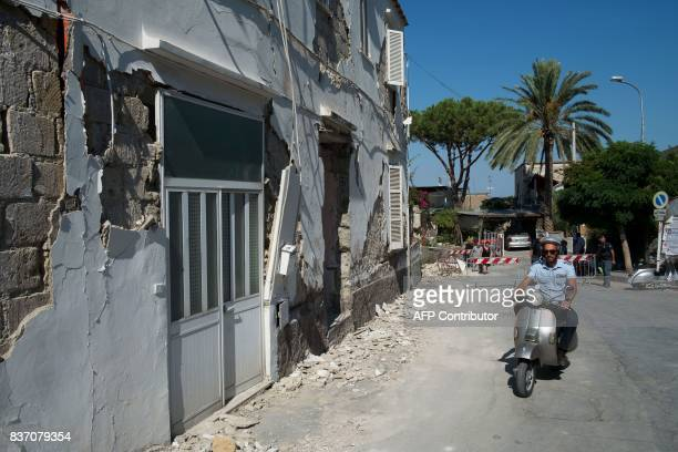 A policeman rides a scooter next to a damaged house in Casamicciola Terme on the Italian island of Ischia on August 22 after an earthquake hit the...