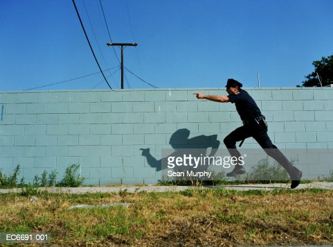 Policeman running next to cement wall, yelling and pointing finger