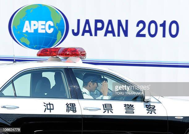 A policeman salutes another during a car patrol in the area around the AsiaPacific Economic Cooperation venue in Yokohama suburban Tokyo on November...