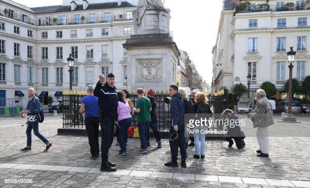 A policeman scatters activists making noise with kitchen utensils during a demonstration called for by La France Insoumise leftist party...