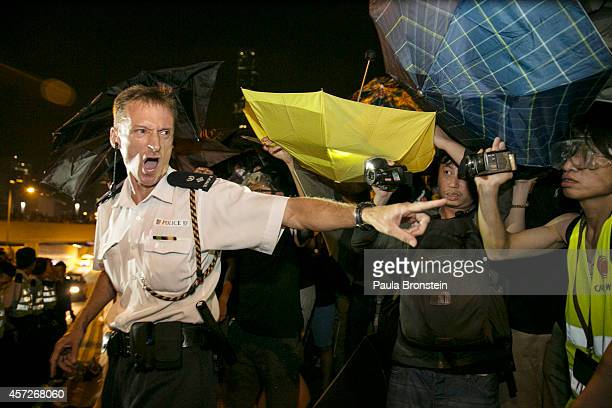 A policeman screams at protesters after scuffles broke out between police and protesters October 16 2014 in Hong Kong Prodemocracy supporters...