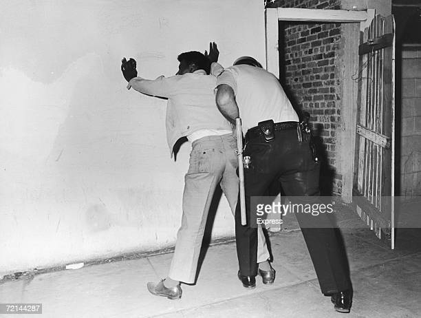 A policeman searches a suspect during rioting in the Watts area of Los Angeles August 1965