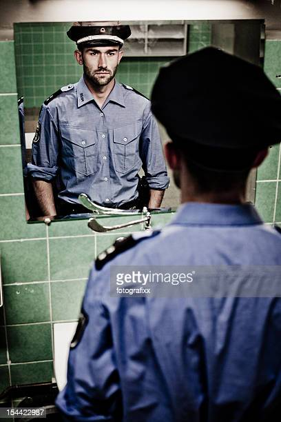 policeman sees himself in a mirror in rotten, abandoned bathroom