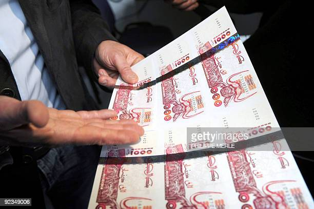 A policeman shows plates of false printed Algerian Dinar banknotes shown during a press conference on October 26 2009 in Lyon central France after...