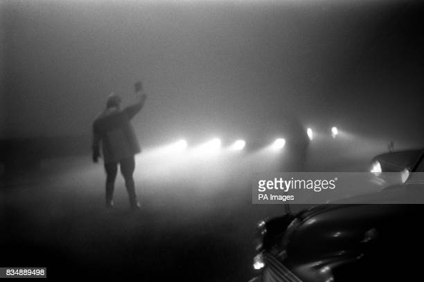 A policeman silhouetted by car headlamps as he tries to sort out rush hour chaos in Bristol when the thickest fog for many years combined with the...