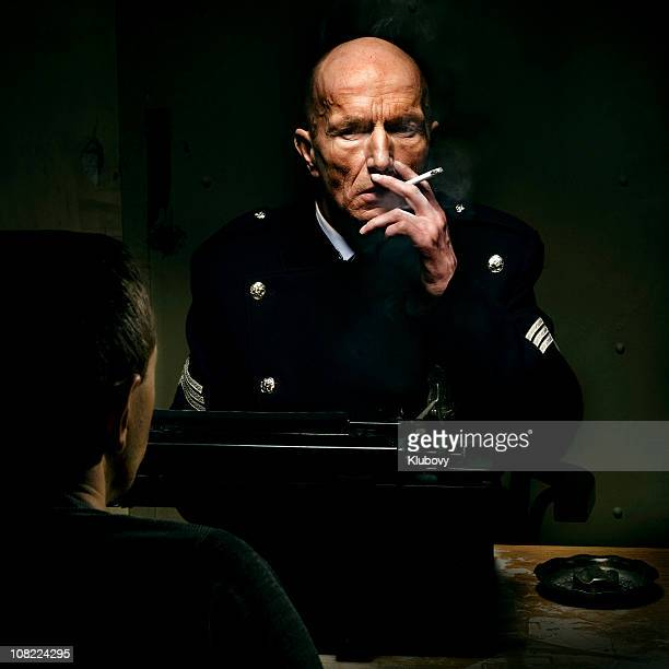 Policeman SItting in Interrogation Room and Smoking