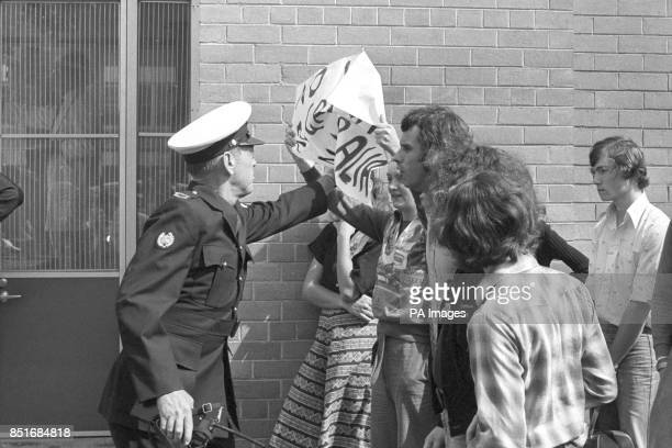 A policeman snatches a banner from a demonstrator outside the Royal Women's Hospital in Melbourne before a visit by the Queen during her Silver...