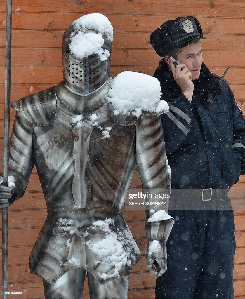 A policeman speaks by mobile phone at a souvenir shop decorated with suits of armour as he sheltered from heavy snow in Kiev on December 11, 2012. AFP PHOTO/ SERGEI SUPINSKY
