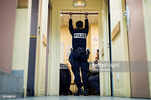 A policeman speaks with his colleagues in the office of the Gare du Nord police station on November 29 2012 AFP PHOTO / FRED DUFOUR