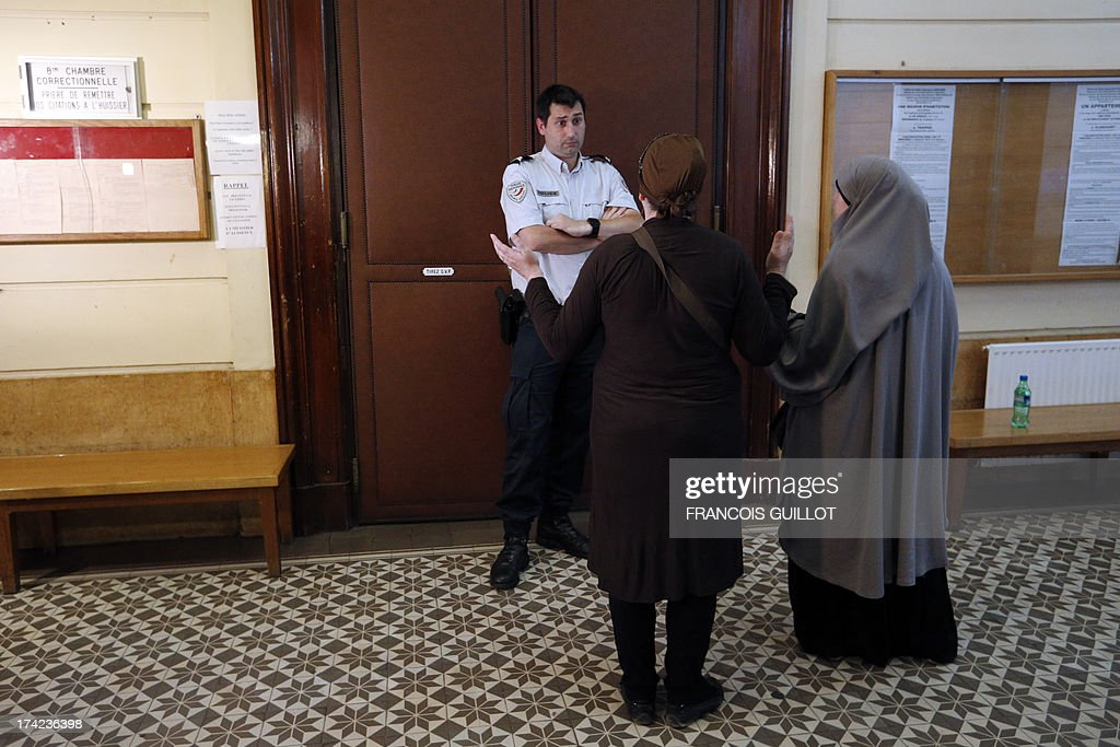 A policeman speaks with two women in front of a courtroom where three men are judged at Versailles' Courthouse, near Paris, on July 22, 2013, for having thrown projectiles on Policemen during unrest in the suburban city of Trappes on July 19 evening. The unrest came after police officers carried out an identity check on a full-face veiled woman and her husband. The woman's husband tried to strangle one of the officers during the check according to Versailles' prosecutor.