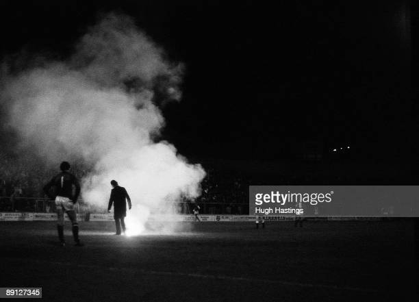A policeman stamps out a flare thrown onto the pitch during the Milk Cup Second Round match between Millwall and Chelsea held on October 9 1984 at...
