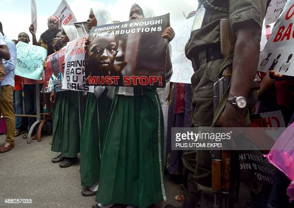 A policeman stand beside children holding as members of Lagos based civil society groups hold rally calling for the release of missing Chibok school...