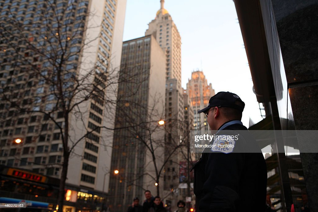 A policeman standing on the sidewalk of Michigan Avenue on his duty in front of a branch of Citibank on the background are the Intercontinental Hotel...