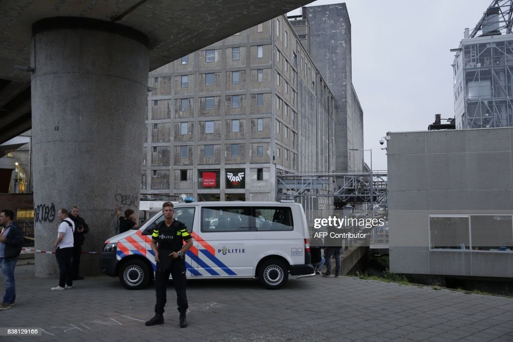 A policeman stands as police evacuate the concert venue Maassilo, after a concert was cancelled because of a terror threat, in Rotterdam, on August 23, 2017. A rock concert in Rotterdam was cancelled on August 23 due to a terror threat involving a Spanish van found with gas bottles inside, the local mayor said. Earlier the Maassilo venue announced that 'due to a terrorist threat, the Allah-Las concert will not take place this evening, on police orders'. Rotterdam police confirmed the decision was taken due to a 'possible terrorist threat' and that the van's driver had been arrested. / AFP PHOTO / ANP / Arie Kievit / Netherlands OUT