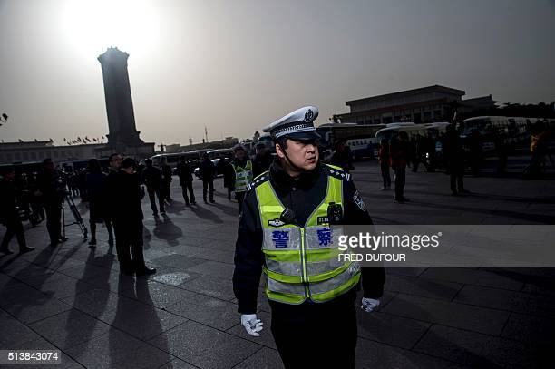 A policeman stands at the Great Hall of the People during the opening ceremony of the National People's Congress in Beijing on March 5 2016 Chinas...