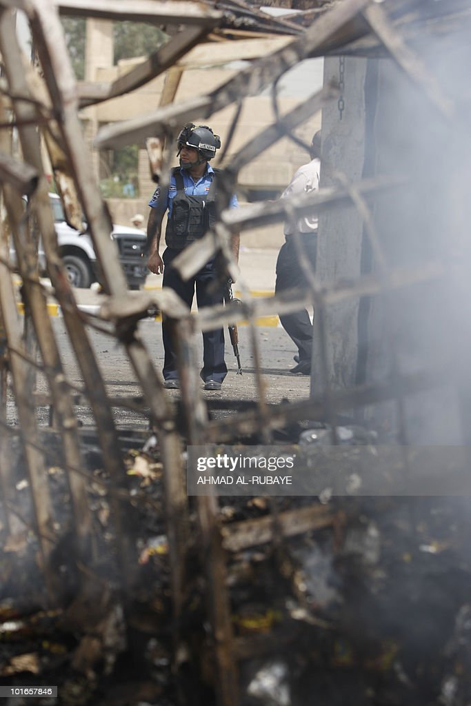 A policeman stands at the scene of a suicide bomb attack outside a police station in Baghdad's Al-Amil district, south of the capital, on June 6, 2010.