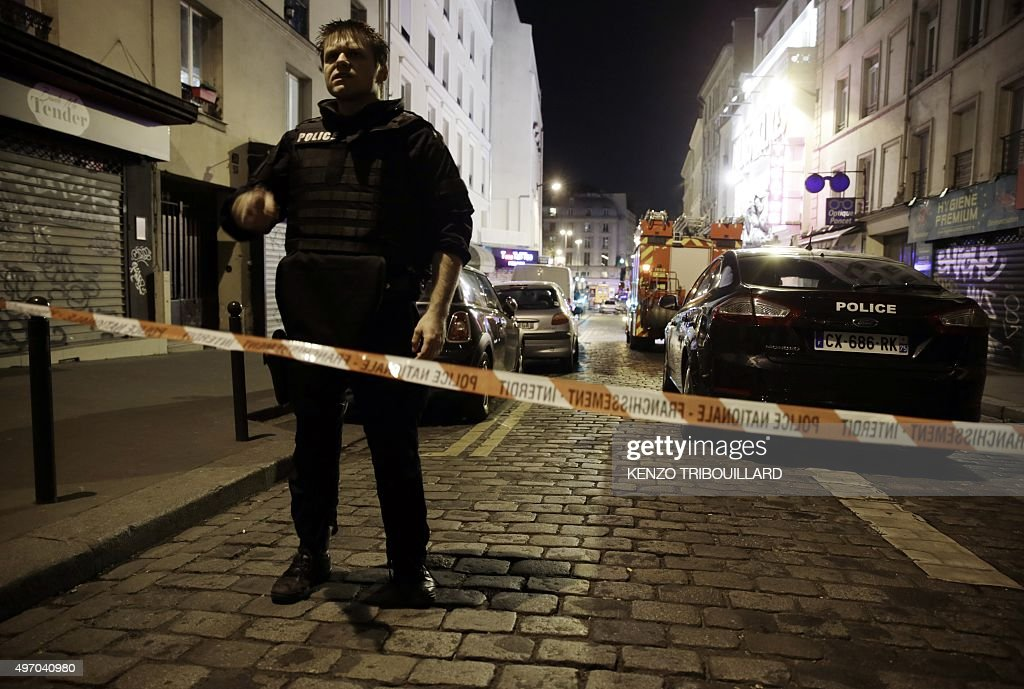 A policeman stands behind a cordon blocking the street near the site of an attack in a restaurant in Paris on November 13 2015 At least 18 people...